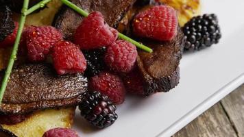 Foto giratoria de un delicioso plato de tocino de pato ahumado con piña asada, frambuesas, moras y miel - comida 107