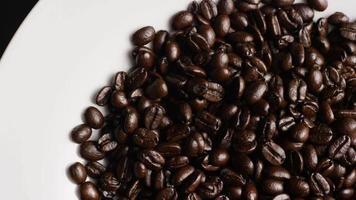 Foto giratoria de deliciosos granos de café tostados sobre una superficie blanca - granos de café 056