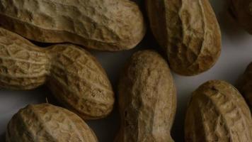 filme cinematográfico giratório de amendoim em uma superfície branca - amendoim 006