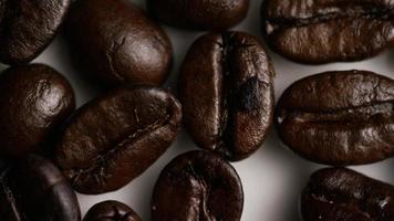 Foto giratoria de deliciosos granos de café tostados sobre una superficie blanca - granos de café 035