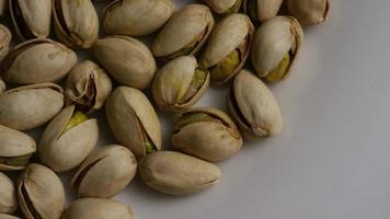 Cinematic, rotating shot of pistachios on a white surface - PISTACHIOS 005