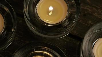 Velas de té con mechas en llamas sobre un fondo de madera - velas 014