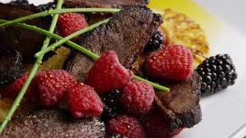 colpo rotante di un delizioso piatto di pancetta affumicata d'anatra con ananas grigliato, lamponi, more e miele - cibo 118