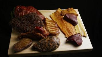 Rotating shot of a variety of delicious, premium smoked meats on a wooden cutting board - FOOD 049