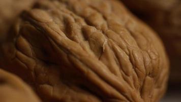 inquadratura cinematografica e rotante di noci con il guscio su una superficie bianca: noci 026 video