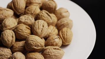 Cinematic, rotating shot of walnuts in their shells on a white surface - WALNUTS 069