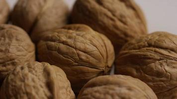 Cinematic, rotating shot of walnuts in their shells on a white surface - WALNUTS 017