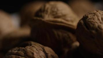 filmische, rotierende Aufnahme von Walnüssen in ihren Schalen auf einer weißen Oberfläche - Walnüsse 091