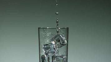líquido transparente carbonatado que se vierte y salpica en cámara ultra lenta (1,500 fps) en un vaso lleno de hielo - líquido vertido 017