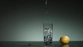 líquido transparente carbonatado que se vierte y salpica en cámara ultra lenta (1,500 fps) en un vaso lleno de hielo - líquido vertido 025