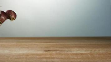 Knoblauchzehenstücke springen in Ultra-Zeitlupe (1.500 fps) auf einer Holzoberfläche - Grillphantom 034