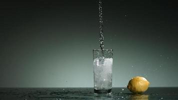 líquido transparente carbonatado que se vierte y salpica en cámara ultra lenta (1,500 fps) en un vaso lleno de hielo - líquido vertido 028