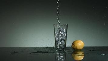 líquido transparente carbonatado que se vierte y salpica en cámara ultra lenta (1,500 fps) en un vaso lleno de hielo - líquido vertido 005