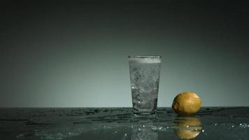 líquido transparente carbonatado que se vierte y salpica en cámara ultra lenta (1,500 fps) en un vaso lleno de hielo - líquido vertido 008