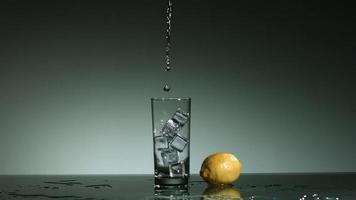 líquido transparente carbonatado que se vierte y salpica en cámara ultra lenta (1,500 fps) en un vaso lleno de hielo - líquido vertido 022