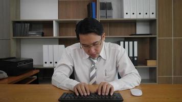 Geschäftsmannangestellter, der Tastatur schreibt und Monitorcomputer betrachtet, während er müde ist