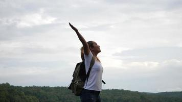 Slow motion of woman with arms raised on the lake and mountain