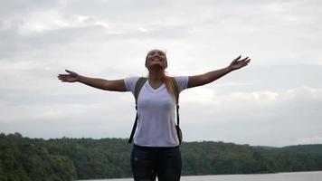 mouvement lent de femme avec les bras levés sur le lac et la montagne video