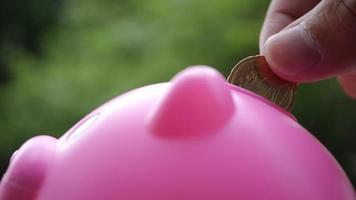 Mano poniendo monedas en una alcancía rosa, ahorrando dinero concepto