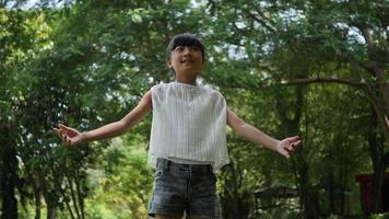 menina asiática brincando ao ar livre em câmera lenta, girando, sorrindo e levantando as mãos no ar video