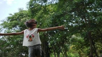 Asian little girl playing outdoor in slow motion, Spinning and smiling and raising hands in the air