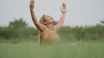 joyeuse femme assise sur le champ vert et levant sa main rafraîchir la vie