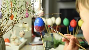 kleines Kind, das Ostereier malt