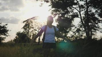 Zeitlupe, junge Frau, die in der Natur reist, steht umgeben von weit geöffneten Naturarmen, nachdem sie einen langen Weg gegangen ist.