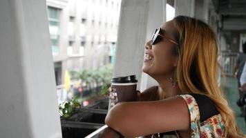 close-up de uma linda mulher degustando café perto da rua