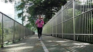 Young asian woman running on sidewalk in morning. Health conscious concept with copy space. Fitness sport people and healthy lifestyle concept.