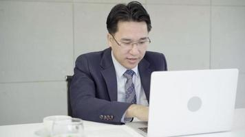 Slow motion - Asian business man coming at office with laptop and documents on his desk, consultant lawyer concept. video