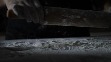 câmera lenta das mãos de uma mulher amassando farinha para pizza