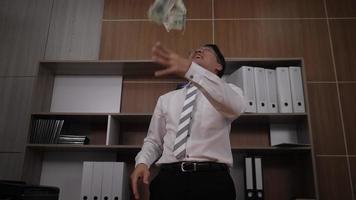 El empresario dispersa los dólares y baila divertido en una oficina.