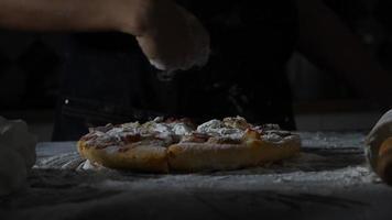 câmera lenta das mãos de uma mulher peneirando farinha sobre uma pizza