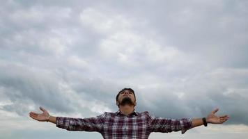 l'homme se tient détendu et levant les mains en l'air au parc video