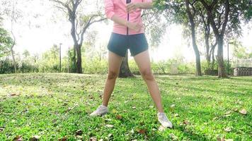 mujer asiática joven sana que ejercita en el parque.