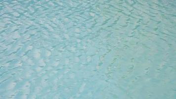 texture de la surface de l'eau, mouvement lent en boucle, ondulations et vagues de la piscine propre, réfraction de la lumière du soleil vue de dessus texture côté mer sable blanc video