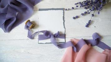 cartão em branco branco, envelope e fita em um fundo de tecido rosa e azul com flores de lavanda em um fundo branco.
