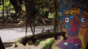 altalena in legno nel parco pubblico con graffiti in background