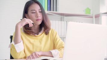 bela jovem sorridente asiática chegando laptop na mesa na sala de estar em casa.