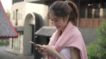 alegre mujer asiática mochilero blogger con smartphone para dirección y mirando en el mapa de ubicación.