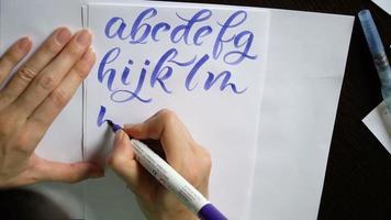 mão de mulher escreve um alfabeto caligráfico video