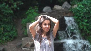jeune femme posant avec une cascade en arrière-plan. video