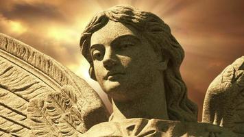 la statue d'un ange sur les nuages d'or time lapse