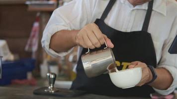 barista vertiendo leche en la taza de café
