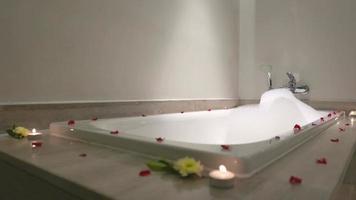 banheira com pétalas de rosa e vela