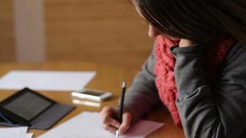 jovem escrevendo em uma folha de papel video