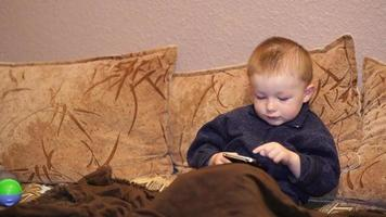 Child Playing With Mobile Phone On The Sofa video