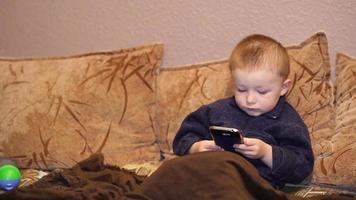 criança brincando com o celular no sofá