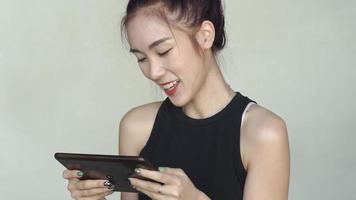 Mujer asiática juega juegos en una tableta digital